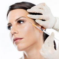 Portrait of beautiful young woman getting botox cosmetic injection in her face over white background.
